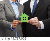 Купить «Мужчина и женщина в деловых костюмах держат в руках вырезанный из бумаги зеленый домик», фото № 5787005, снято 12 декабря 2013 г. (c) Syda Productions / Фотобанк Лори