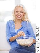 Купить «Молодая привлекательная девушка с миской попкорна», фото № 5787037, снято 6 февраля 2014 г. (c) Syda Productions / Фотобанк Лори