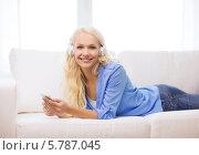 Купить «Симпатичная девушка в домашней одежде лежит на диване в наушниках и с сотовым телефоном в руках», фото № 5787045, снято 6 февраля 2014 г. (c) Syda Productions / Фотобанк Лори