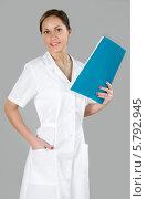 Купить «Стройная медсестра в белом халате стоит на сером фоне и держит в руке папку», фото № 5792945, снято 5 марта 2014 г. (c) safonovstudio / Фотобанк Лори