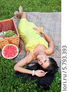 Молодая красивая девушка лежит на спине рядом с корзиной для пикника. Стоковое фото, фотограф Виктория Чеканова / Фотобанк Лори