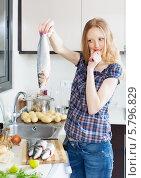 Купить «Блондинка стоит на кухне с рыбой в руке и думает, что приготовить», фото № 5796829, снято 15 мая 2013 г. (c) Яков Филимонов / Фотобанк Лори