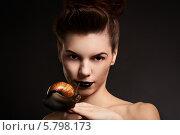 Портрет девушки с черными губами с улиткой на руке на темном фоне. Стоковое фото, фотограф Евгения Семенова / Фотобанк Лори
