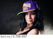 Сексуальная брюнетка в яркой кепке и черной майке с большой золотой цепью на шее, на темном фоне. Стоковое фото, фотограф Евгения Семенова / Фотобанк Лори