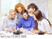 Купить «Молодые коллеги в офисе обсуждают фотографии. Фотоаппарат лежит на столе», фото № 5801005, снято 1 февраля 2014 г. (c) Syda Productions / Фотобанк Лори