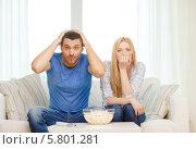 Купить «Молодые мужчина и женщина сидят дома перед телевизором с миской покорна», фото № 5801281, снято 9 февраля 2014 г. (c) Syda Productions / Фотобанк Лори