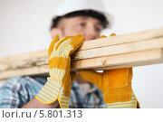 Купить «Рабочий в перчатках переносит деревянные доски на плече», фото № 5801313, снято 28 января 2014 г. (c) Syda Productions / Фотобанк Лори