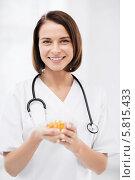 Купить «Позитивная улыбающаяся женщина-врач держит капсулы с витаминами в руках», фото № 5815433, снято 6 июля 2013 г. (c) Syda Productions / Фотобанк Лори