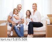 Купить «Семейный отдых дома. Родители с двумя детьми дома на диване», фото № 5815509, снято 1 марта 2014 г. (c) Syda Productions / Фотобанк Лори