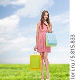 Купить «Девушка в розовом платье стоит в полный рост на фоне голубого неба и держит в руках сумки с покупками», фото № 5815833, снято 26 февраля 2014 г. (c) Syda Productions / Фотобанк Лори