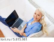 Купить «Девушка в наушниках сидит на диване с ноутбуком, вид сверху», фото № 5815981, снято 6 февраля 2014 г. (c) Syda Productions / Фотобанк Лори