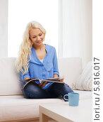 Купить «Привлекательная молодая женщина сидит на диване, поджав ноги и листает журнал», фото № 5816017, снято 6 февраля 2014 г. (c) Syda Productions / Фотобанк Лори