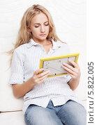 Девушка сидит на диване и смотрит на фотографию в рамке. Стоковое фото, фотограф Гладских Татьяна / Фотобанк Лори
