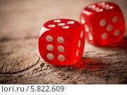 Купить «Игральные красные кубики на деревянном фоне», фото № 5822609, снято 10 марта 2014 г. (c) Майя Крученкова / Фотобанк Лори