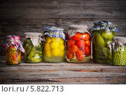Купить «Консервированные овощи на деревянном фоне», фото № 5822713, снято 5 апреля 2014 г. (c) Майя Крученкова / Фотобанк Лори