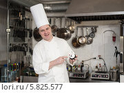 Шеф-повар держит в руках настольный звонок, на кухне. Стоковое фото, фотограф Галина Попова / Фотобанк Лори