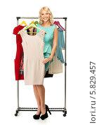 Купить «Весёлая красивая блондинка держит платье на вешалке», фото № 5829457, снято 15 апреля 2014 г. (c) Andrejs Pidjass / Фотобанк Лори