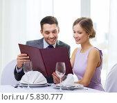 Купить «Вечер в ресторане. Парень и девушка выбирают блюда к ужину, просматривая меню», фото № 5830777, снято 9 марта 2014 г. (c) Syda Productions / Фотобанк Лори