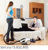 Купить «Жена пылесосит, а муж лежит на диване с ноутбуком», фото № 5832805, снято 12 марта 2014 г. (c) Яков Филимонов / Фотобанк Лори