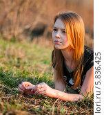Купить «Задумчивая девочка-подросток с рыжими волосами при вечернем солнце лежит на земле», эксклюзивное фото № 5836425, снято 20 апреля 2014 г. (c) Игорь Низов / Фотобанк Лори