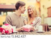 Романтическое свидание влюбленной пары в кафе. Парень дарит девушке подарок и цветы. Стоковое фото, фотограф Syda Productions / Фотобанк Лори