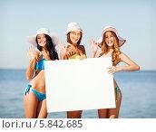 Купить «Три девушки в летних шляпах стоят на пляже с пустым баннером в руках», фото № 5842685, снято 11 июля 2013 г. (c) Syda Productions / Фотобанк Лори