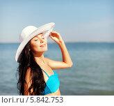 Девушка в элегантной белой шляпе загорает на берегу моря. Стоковое фото, фотограф Syda Productions / Фотобанк Лори
