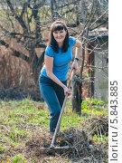 Купить «Весёлая женщина-дачница граблями убирает старую траву на участке», эксклюзивное фото № 5843885, снято 20 апреля 2014 г. (c) Игорь Низов / Фотобанк Лори