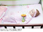 Купить «Маленькая малышка в розовом комбинезоне лежит в детской кроватке», фото № 5846997, снято 18 апреля 2011 г. (c) Кекяляйнен Андрей / Фотобанк Лори
