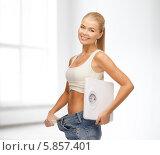 Купить «Девушка с напольными весами в больших джинсах улыбается, радуясь снижению веса», фото № 5857401, снято 23 марта 2013 г. (c) Syda Productions / Фотобанк Лори