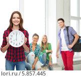 Купить «Девушка в школе держит в руках настенные часы с большим циферблатом», фото № 5857445, снято 26 февраля 2014 г. (c) Syda Productions / Фотобанк Лори