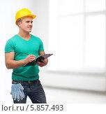 Купить «Мужчина в зеленой футболке и желтой каске делает записи», фото № 5857493, снято 16 февраля 2014 г. (c) Syda Productions / Фотобанк Лори