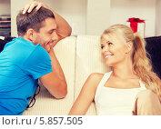 Купить «Молодые мужчина и женщина смотрят друг на друга, сидя дома на диване», фото № 5857505, снято 14 декабря 2018 г. (c) Syda Productions / Фотобанк Лори