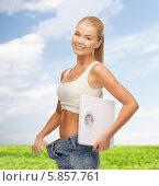 Купить «Очаровательная стройная блондинка в больших джинсах держит напольные весы», фото № 5857761, снято 23 марта 2013 г. (c) Syda Productions / Фотобанк Лори