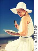 Купить «Девушка в светлом платье и шляпе с широкими полями совершает покупки онлайн, сидя на улице с планшетным компьютером и кредитной карточкой», фото № 5857869, снято 19 июня 2013 г. (c) Syda Productions / Фотобанк Лори