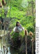 Молодая женщина сидит на траве на берегу ручья. Стоковое фото, фотограф Николай Тоцкий / Фотобанк Лори