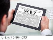 деловой мужчина читает газету на цифровом планшете. Стоковое фото, фотограф Андрей Попов / Фотобанк Лори