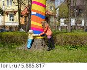 """Купить «Молодая женщина с ребенком играют около """"одетого"""" дерева в Калининграде», фото № 5885817, снято 18 апреля 2014 г. (c) Ирина Борсученко / Фотобанк Лори"""
