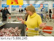 Купить «Женщина у прилавка с мясной кулинарией разводит руками», эксклюзивное фото № 5886245, снято 4 апреля 2014 г. (c) Татьяна Юни / Фотобанк Лори