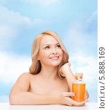 Купить «Счастливая блондинка с бутылочкой массажного масла в руках на фоне голубого неба», фото № 5888169, снято 7 января 2014 г. (c) Syda Productions / Фотобанк Лори