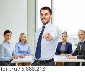 Купить «Привлекательный бизнесмен в светлой рубашке указывает пальцем вперед, стоя перед коллегами в офисе», фото № 5888213, снято 15 марта 2014 г. (c) Syda Productions / Фотобанк Лори