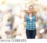 Купить «Девушка в клетчатой рубашке и в джинсах показывает жест одобрения обеими руками», фото № 5888653, снято 12 февраля 2014 г. (c) Syda Productions / Фотобанк Лори