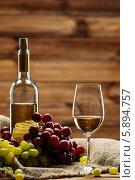 Виноград, белое вино в бутылке и бокале на фоне деревянной стены. Стоковое фото, фотограф Andrejs Pidjass / Фотобанк Лори