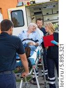 Парамедики завозят носилки с пациентом в машину скорой помощи. Стоковое фото, фотограф CandyBox Images / Фотобанк Лори