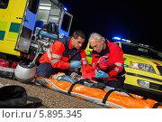 Купить «Парамедики оказывают первую помощь раненой мотоциклистке на дороге», фото № 5895345, снято 11 сентября 2012 г. (c) CandyBox Images / Фотобанк Лори