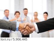 Купить «Деловое рукопожатие на фоне коллектива сотрудников в офисе», фото № 5906445, снято 12 декабря 2013 г. (c) Syda Productions / Фотобанк Лори