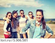 Купить «Счастливая девушка в джинсовой куртке стоит перед компанией веселых друзей на улице летним днем», фото № 5906581, снято 20 июля 2013 г. (c) Syda Productions / Фотобанк Лори
