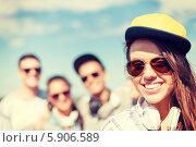 Купить «Девушка в солнцезащитных очках и бейсболке на фоне своих друзей», фото № 5906589, снято 20 июля 2013 г. (c) Syda Productions / Фотобанк Лори