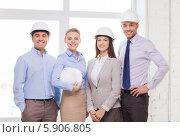 Купить «Группа счастливых деловых людей в белых строительных касках стоит возле окна в офисе», фото № 5906805, снято 5 апреля 2014 г. (c) Syda Productions / Фотобанк Лори
