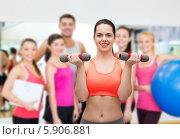 Девушка выполняет упражнения с гантелями в спортивном зале. Стоковое фото, фотограф Syda Productions / Фотобанк Лори
